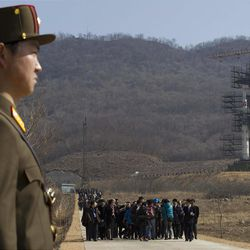A crowd of media gather around a North Korean official on a road in front of North Korea's Unha-3 rocket, slated for liftoff between April 12-16, stands at Sohae Satellite Station in Tongchang-ri, North Korea on Sunday April 8, 2012. North Korean space officials have moved a long-range rocket into position for this week's controversial satellite launch, vowing Sunday to push ahead with their plans in defiance of international warnings against violating a ban on missile activity.(AP Photo/David Guttenfelder)