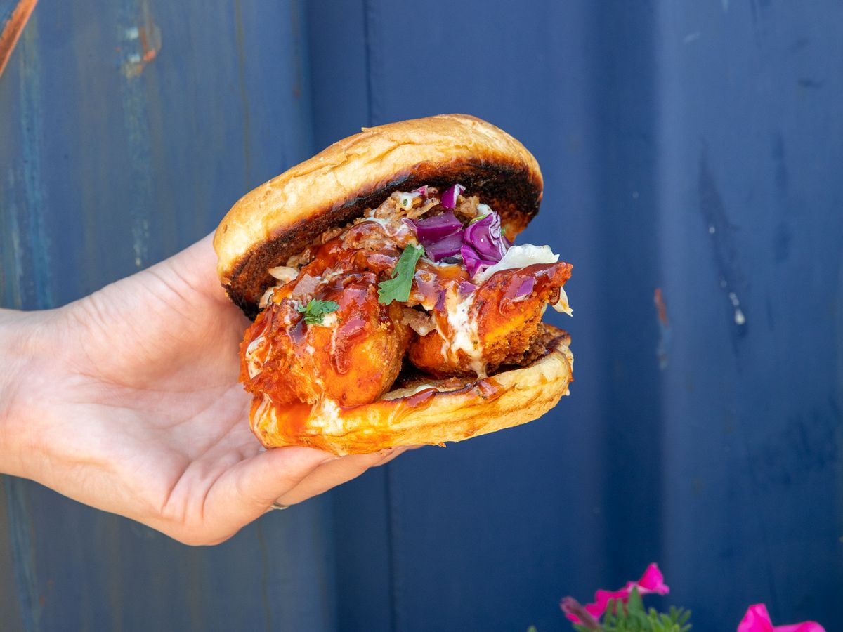 A spicy chicken sandwich with purple cabbage slaw held in front of a purple wall above some pink flowers at Detroit Shipping Co.