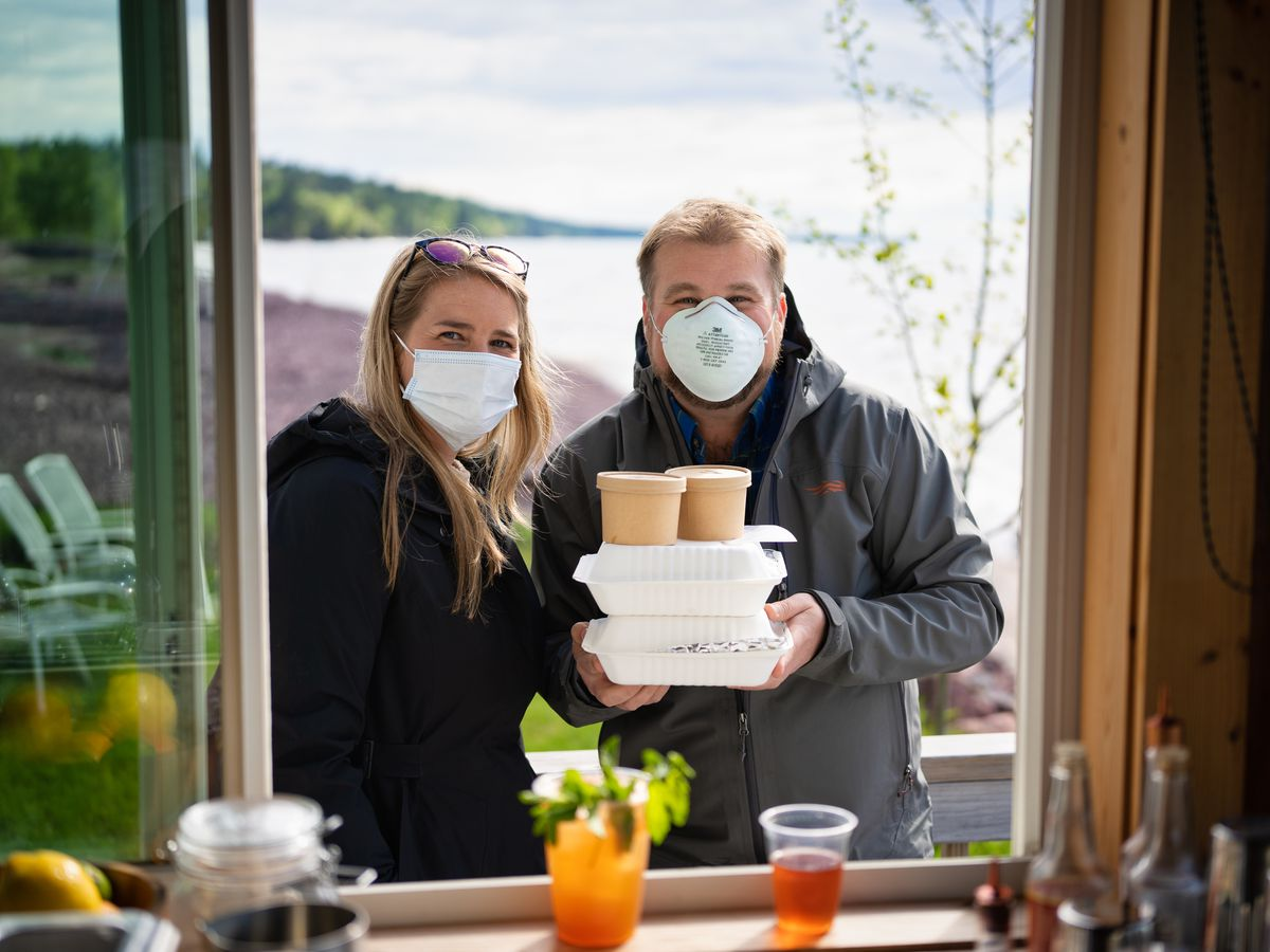 Two customers stand together in front of an open window wearing masks and holding up their takeout boxes.