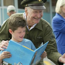 """Col. Gail Halvorsen, the """"Candy Bomber"""", at North Park Elementary School in Tremonton, Utah May 16, 2002, looks at the book about him with Garrett Fronk, at a school assembly and """"candy drop"""" from a plane."""
