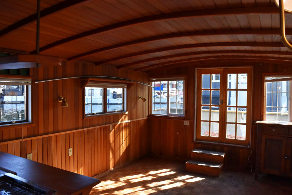 A small living room on a boat with French doors and multiple windows. All the walls are wood.