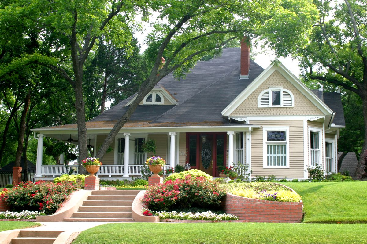 A classic home with a red front door, healthy green lawn, and flower pots.