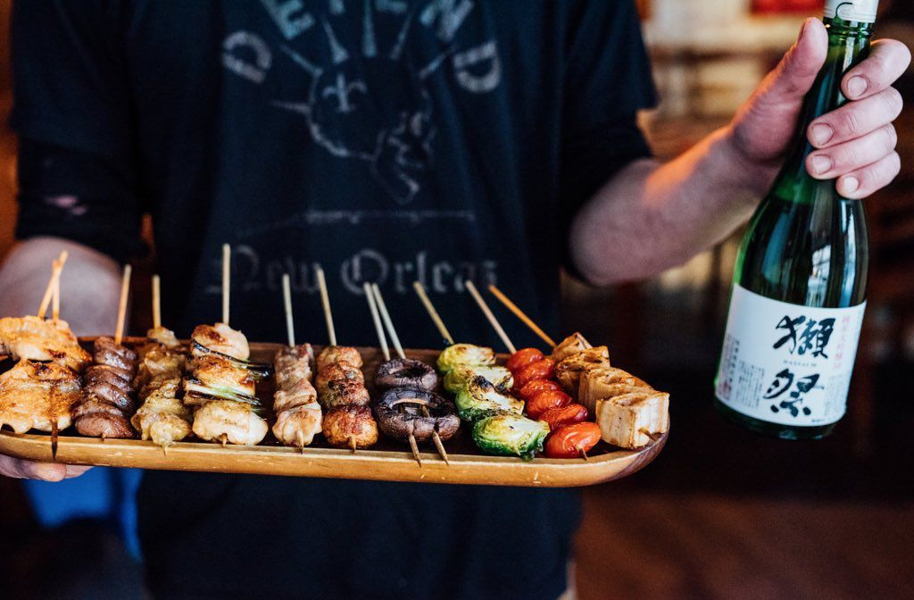 A tray of yakitori skewers with someone holding a bottle of sake next to it.