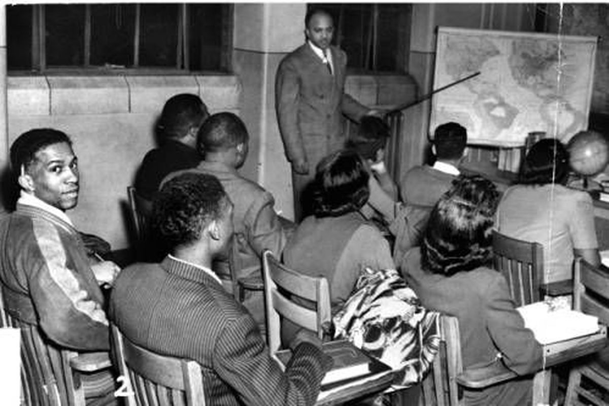 Students sit at their desks at Crispus Attucks High School in 1948 and face the front of the classroom where the teacher is pointing at a map.