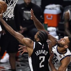 Los Angeles Clippers forward Kawhi Leonard, left, shoots as Utah Jazz center Rudy Gobert defends during the second half of Game 3 of a second-round NBA basketball playoff series Saturday, June 12, 2021, in Los Angeles.