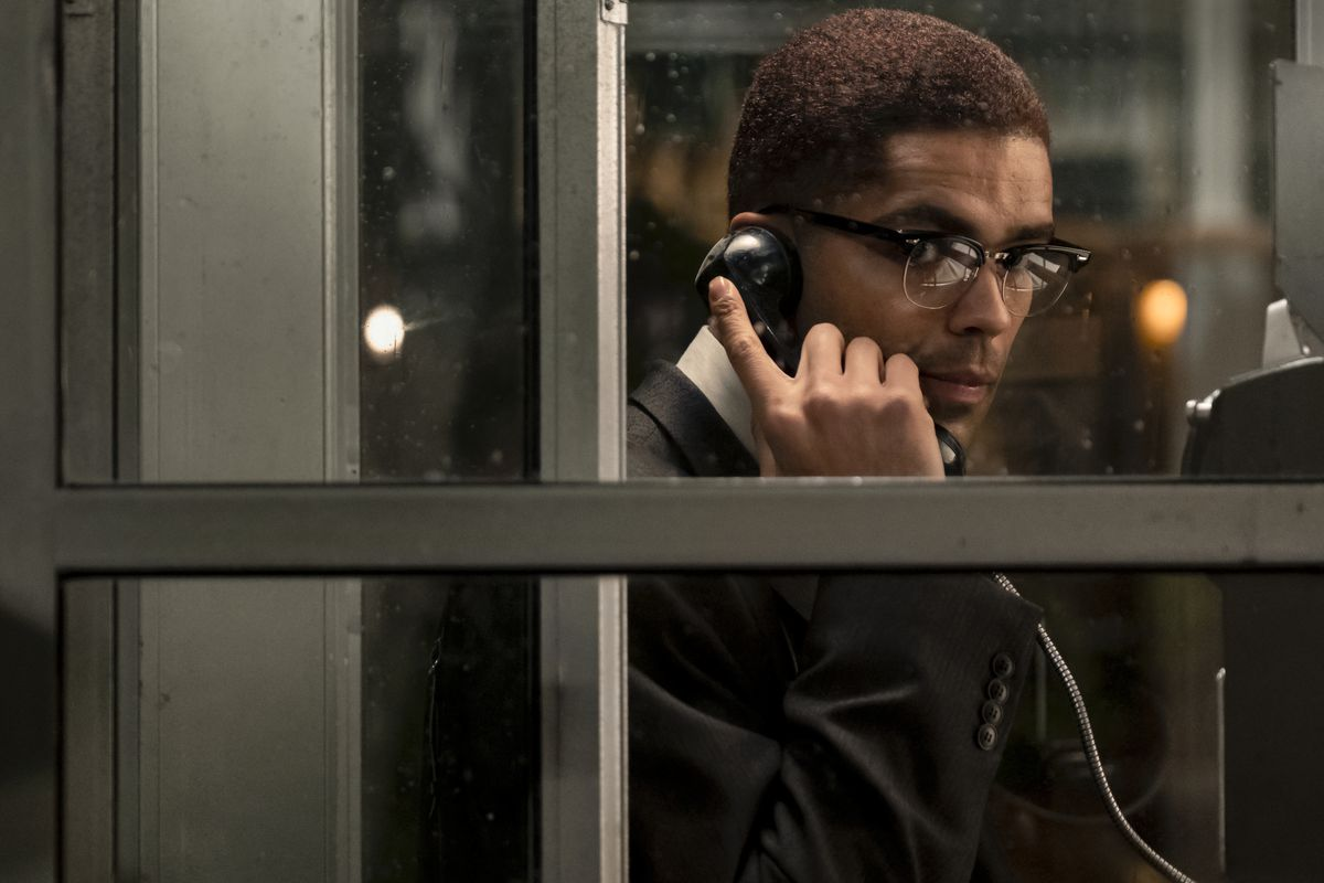 As Malcolm X, Kingsley Ben-Adir holds a payphone to his ear and peers