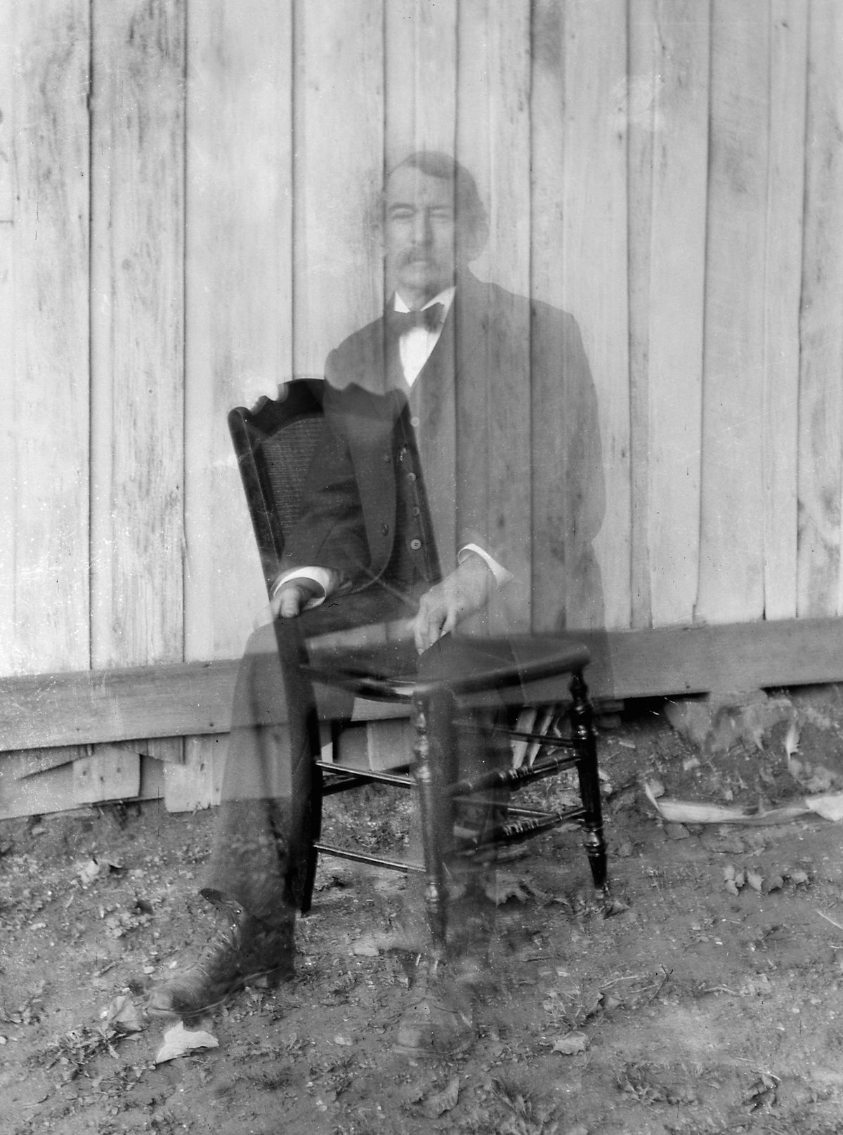 Double exposure of a man on a chair, ca. 1900.