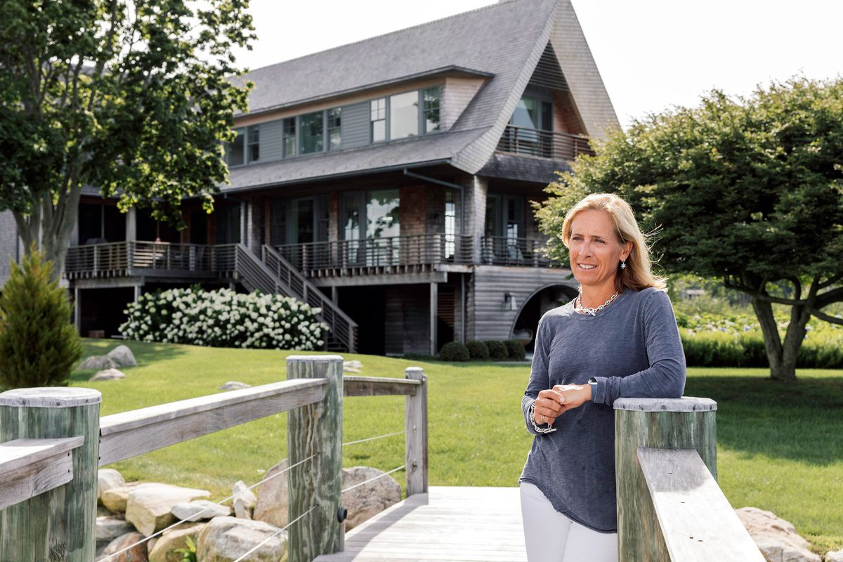 The owner of the house, Jeanne Blasberg, stands in front of her shingle-style home.