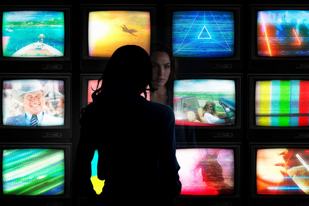 Diana Prince (Gal Gadot) looking at a wall of 12 TVs in Wonder Woman 1984