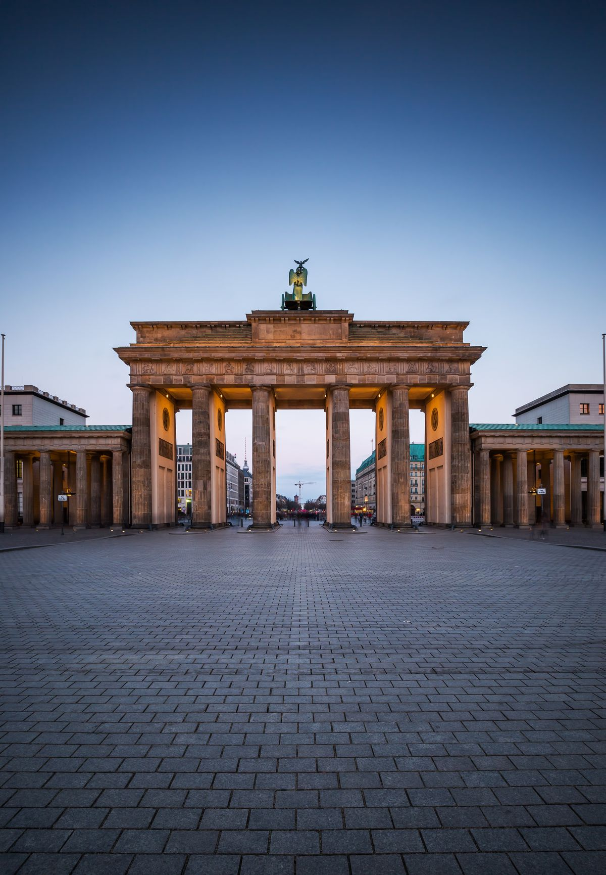 An exterior view of the Brandenburg Gate in Germany. The gate has tall columns and a statue on top.