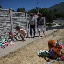 Ava Linsenmeyer, 5, places flowers at a memorial to the victims of Tuesday's fatal shooting on Alta Canyon Drive in Sandy on Wednesday, June 7, 2017. Linsenmeyer is a kindergarten classmate of Jase Rackley, who was killed in Tuesday's shooting. With Linsenmeyer are her mother, Toni Linsenmeyer, and grandmother, Noemi Simons.