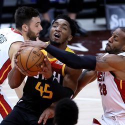 Utah Jazz guard Donovan Mitchell (45) drives to the hoop with Miami Heat forward Andre Iguodala (28) defending on the play as the Utah Jazz and the Miami Heat play an NBA basketball game at Vivint Smart Home Arena in Salt Lake City on Saturday, Feb. 13, 2021.