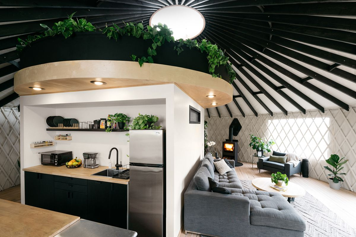 The interior of a yurt features a rectangular structure that houses a bathroom and kitchen. On top of the structure is a circular lofted bed area filled with greenery.