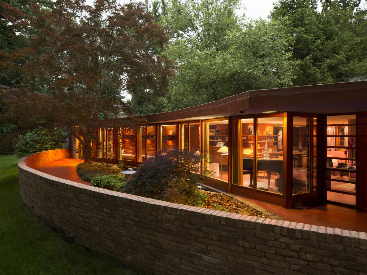 The Kenneth and Phyllis Laurent House by Frank Lloyd Wright.  There is a red brick fence. The house is one level with many windows. The lights are on in the house illuminating the outside area. There are trees surrounding the house.