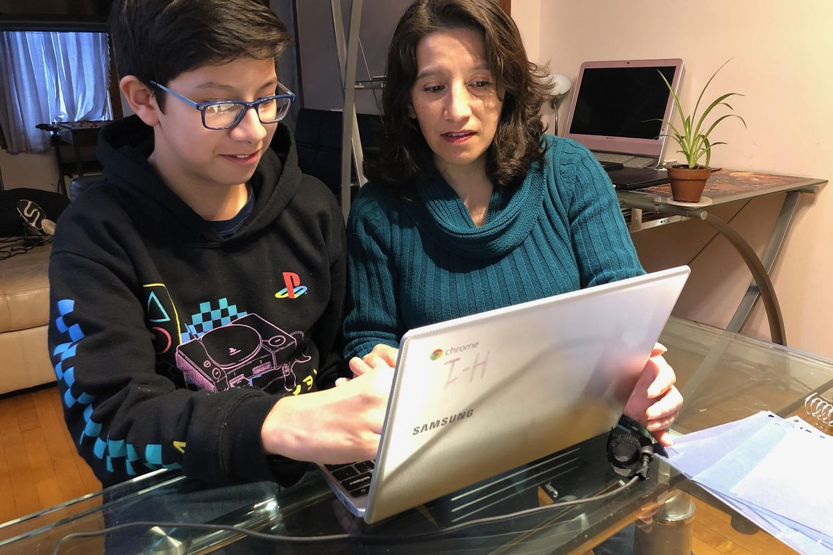 Gabriela Oria helps her son, Alex, a seventh-grader at Madero Middle School, with school work in their Little Village home.