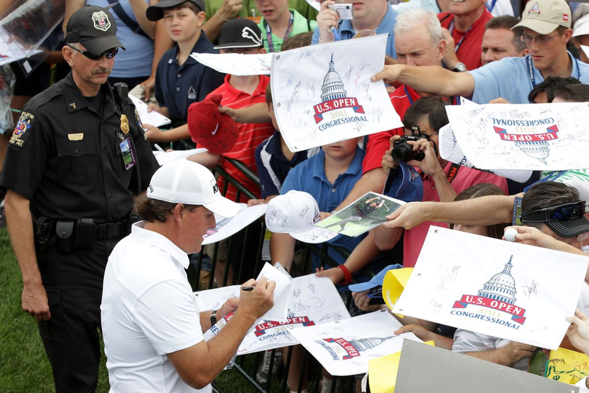 BETHESDA, MD - JUNE 14:  Phil Mickelson signs his autograph for fans during a practice round prior to the start of the 111th U.S. Open at Congressional Country Club on June 14, 2011 in Bethesda, Maryland.  (Photo by Ross Kinnaird/Getty Images)