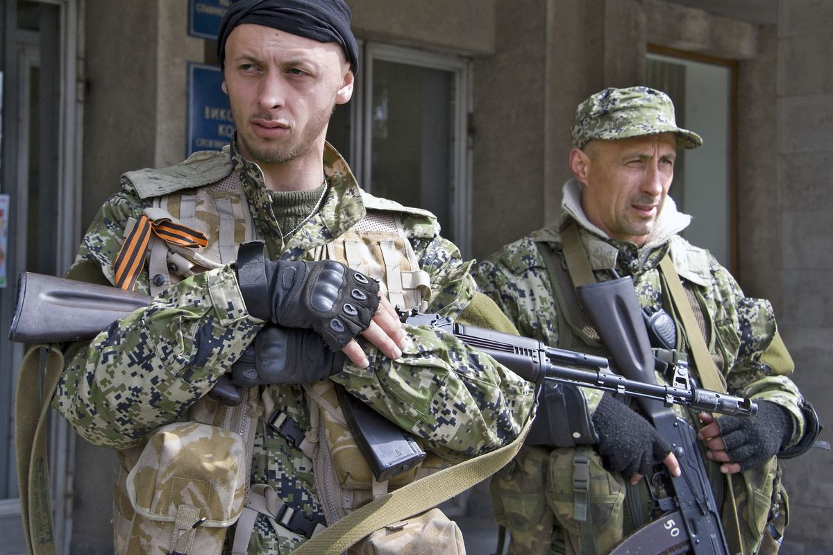 Pro-Russian separatist soldiers guard a seized government building in Slovyansk, Ukraine