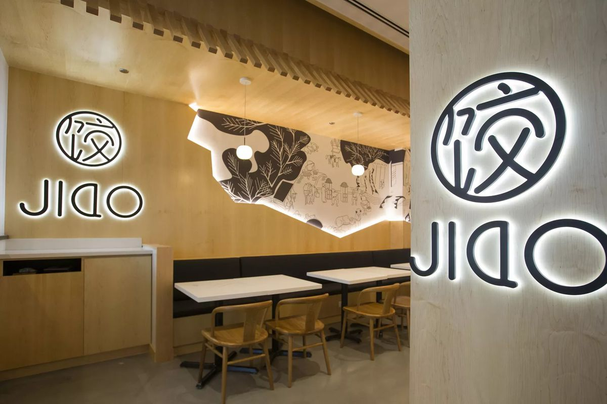 """A dining room entrance with blond wood and large black signs that read """"JIAO."""""""