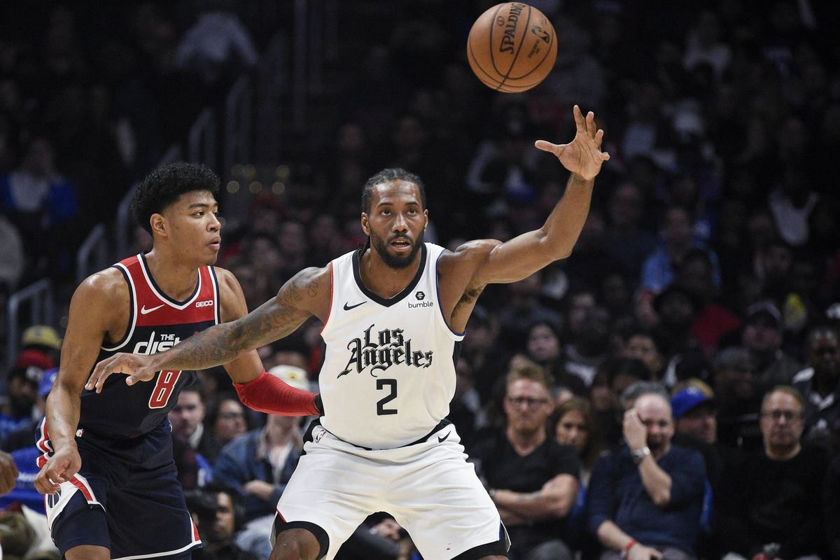 LA Clippers forward Kawhi Leonard reaches for a pass while Washington Wizards forward Rui Hachimura defends during the third quarter at Staples Center.