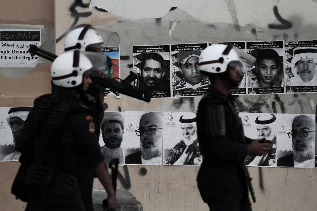 Bahraini riot policemen look for anti-government protesters during clashes in Sitra, Bahrain, Monday, Sept. 3, 2012. Pictures of people killed in the unrest and of jailed political leaders are plastered on the wall. Verdicts are expected Tuesday for numer