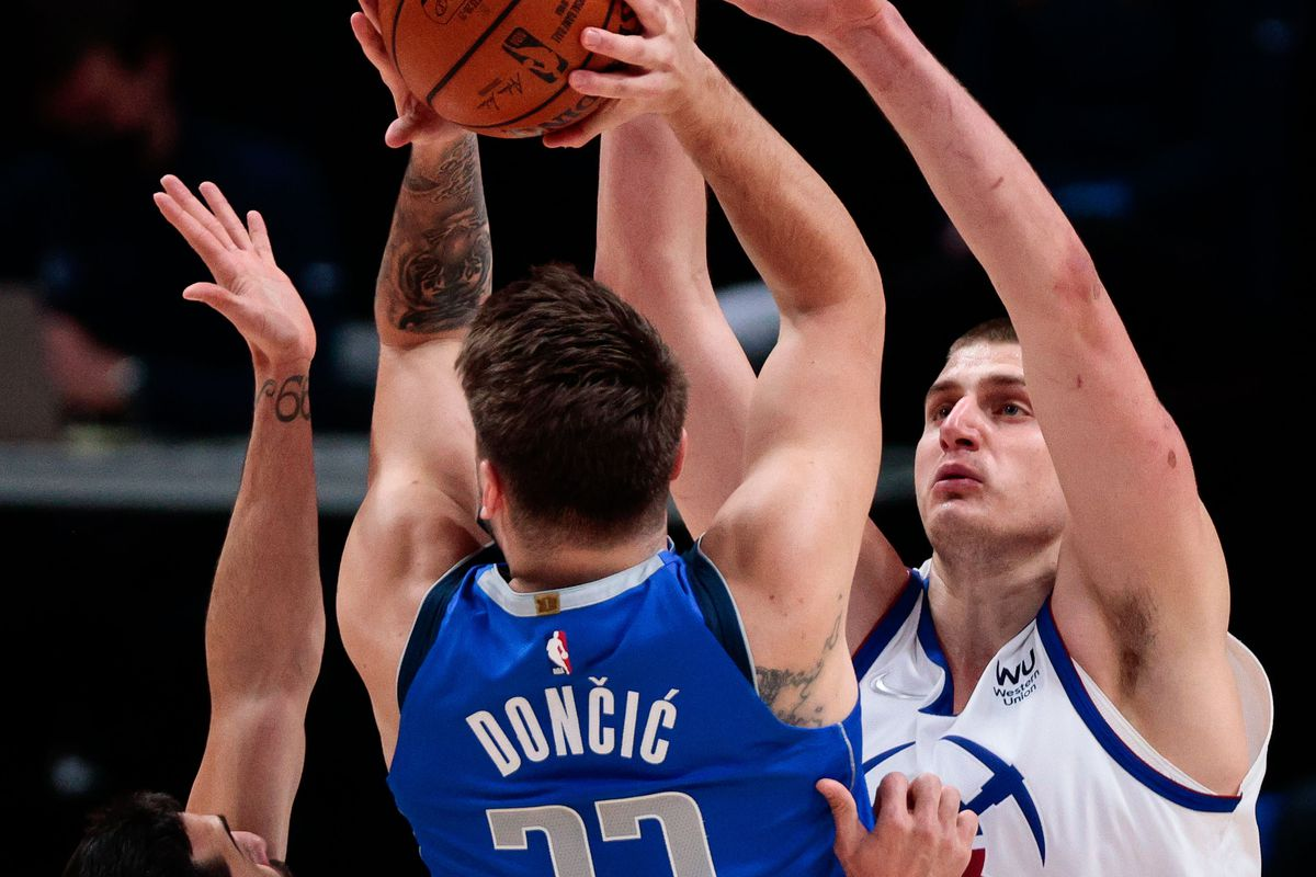 Dallas Mavericks guard Luka Doncic (77) is double teamed by Denver Nuggets center Nikola Jokic (15) and guard Facundo Campazzo (7) in the first quarter at Ball Arena.