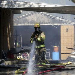 A Unified firefighter works at the scene of a house fire in Millcreek on Thursday, July 9, 2020. The fire is the third structure fire on this block in a week. Four houses in total have been damaged in the week's fires.