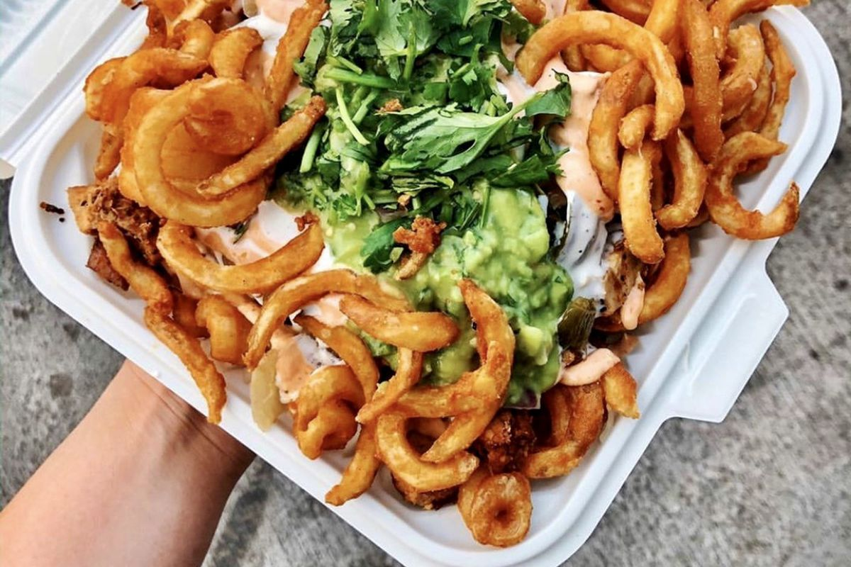 a hand holding a styrofoam container of loaded curly fries, topped with cheese, guacamole and cilantro