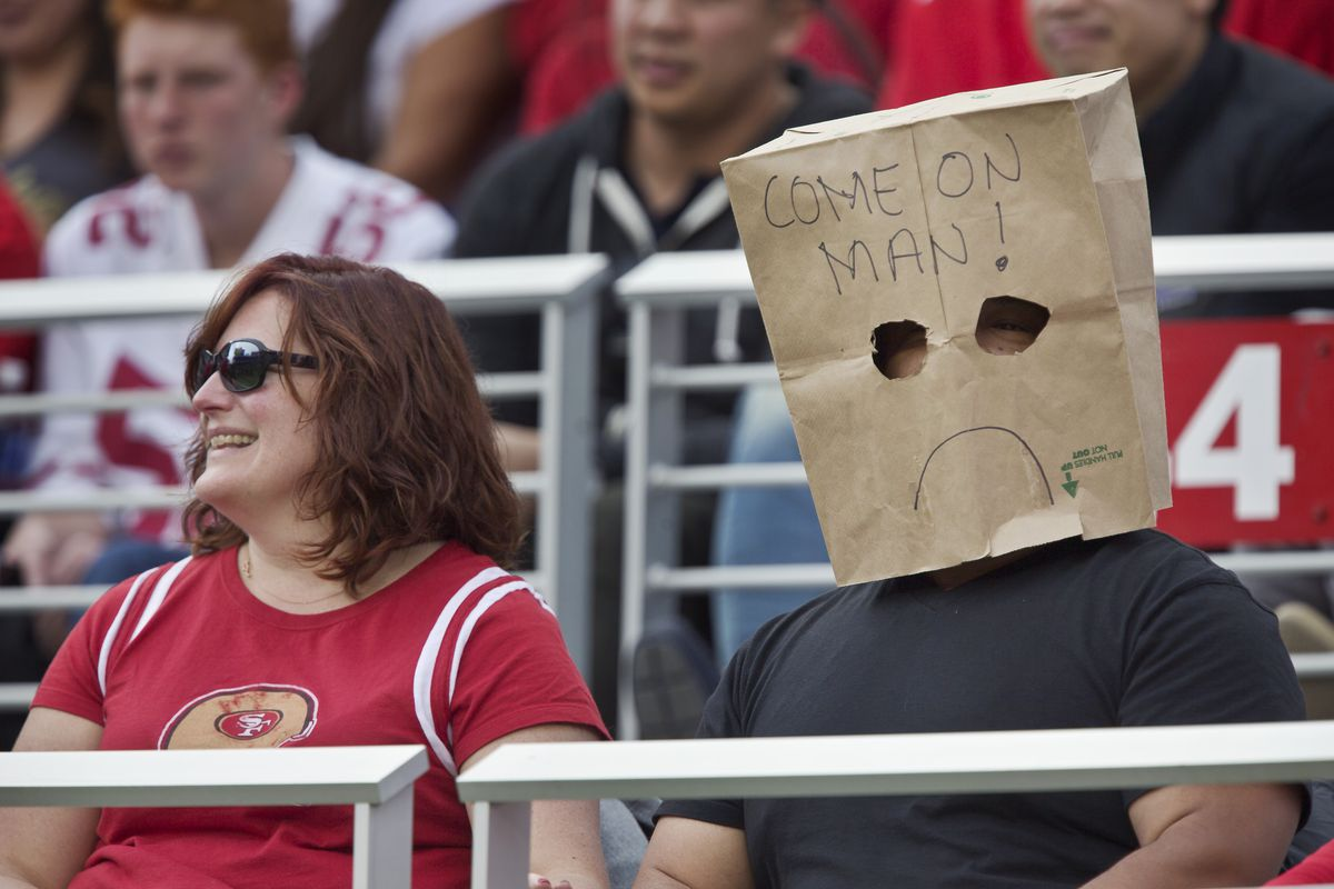 a football fan sitting in the stadium wearing a paper bag over his head
