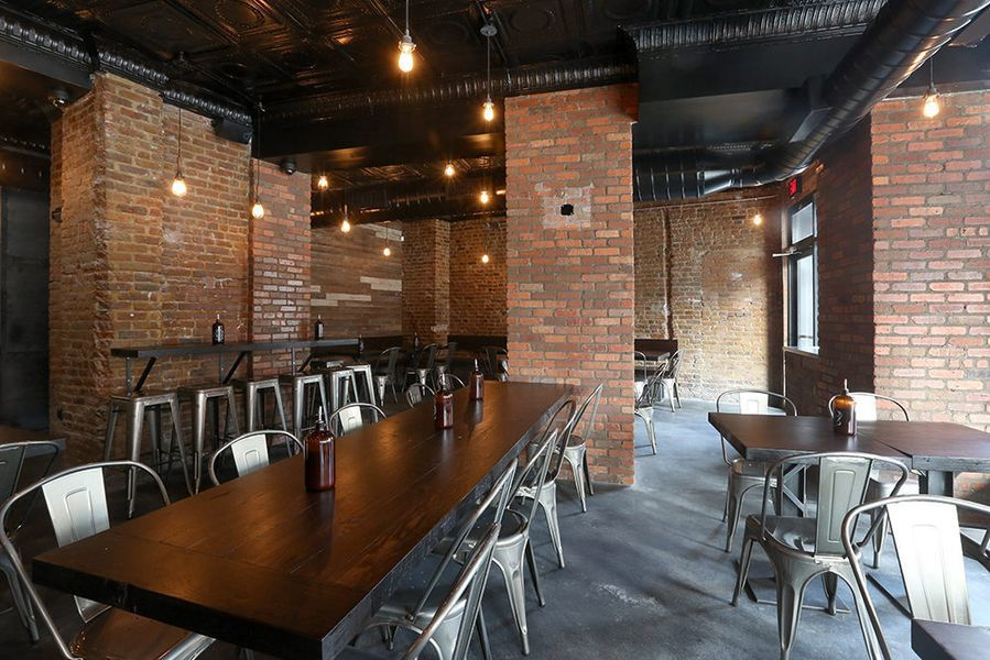 Long wooden tables with steel seats inside an exposed brick space