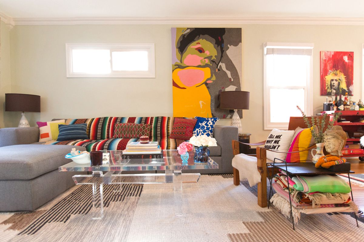 A sofa with a bright patterned blanket in the background of this photo of a living room. A lucite coffee table is the focus of the shot.