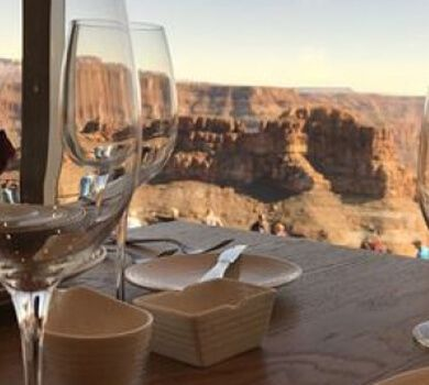 Wine glasses on a table near a window overlooking the Grand Canyon