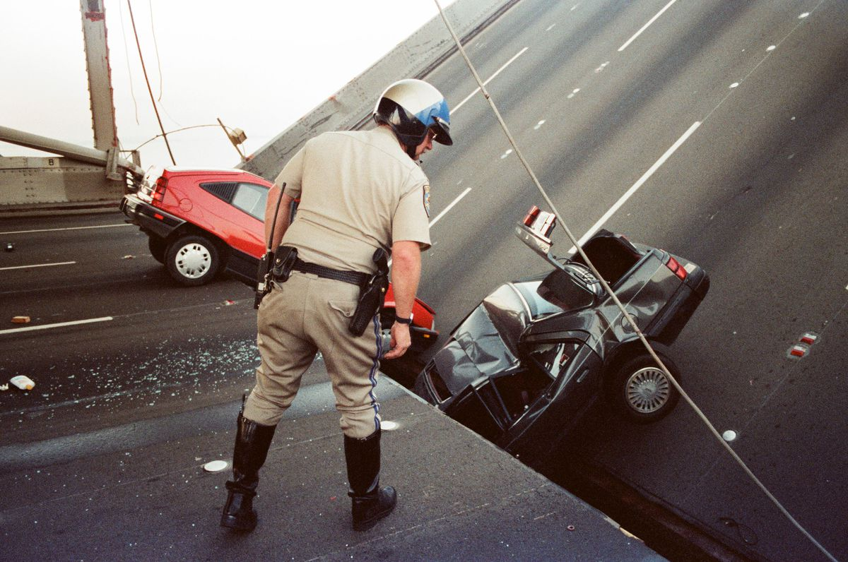 A police officer inspects the fallen part of the bridge that a car has crashed into.
