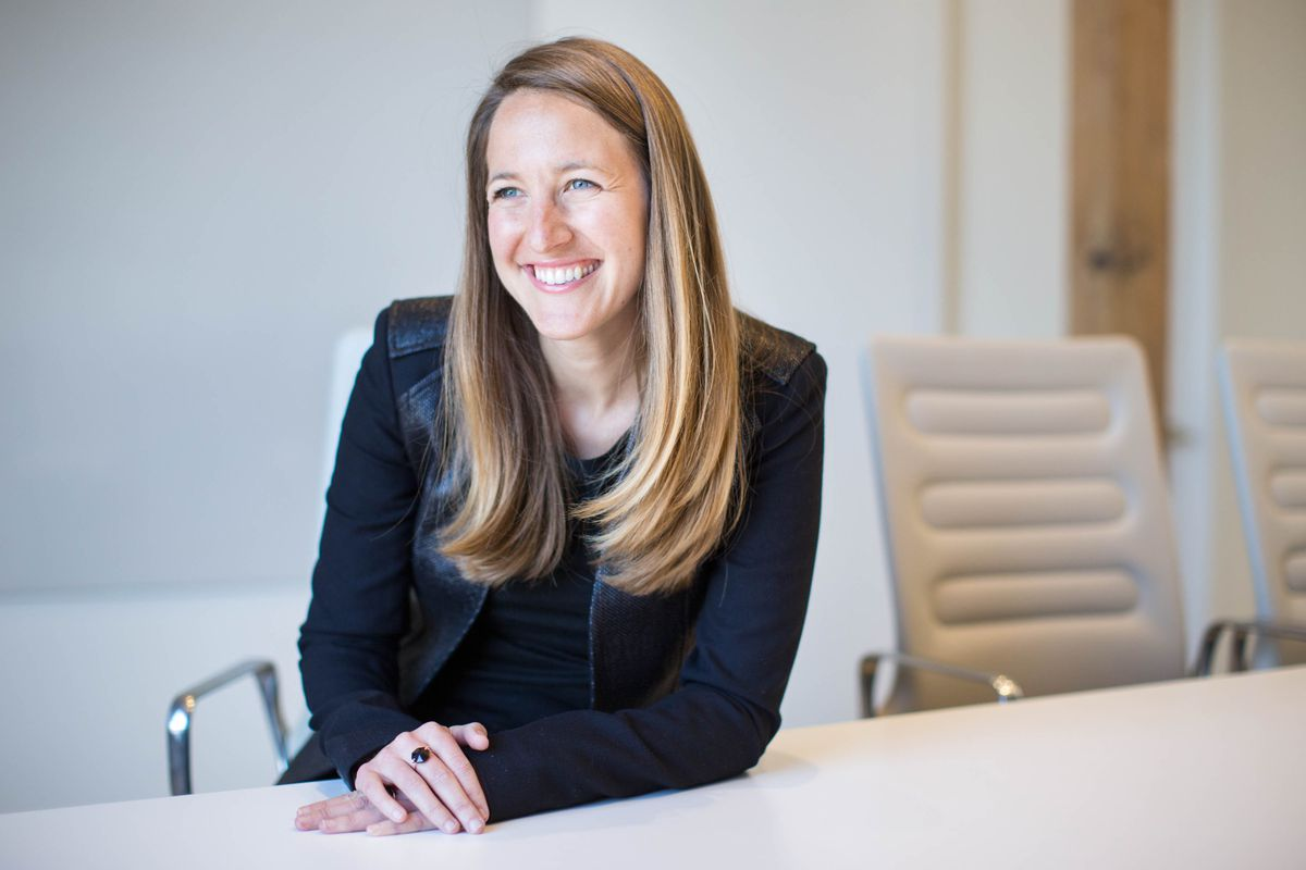 Investor Sarah Cannon sits for a photo at a meeting room table.
