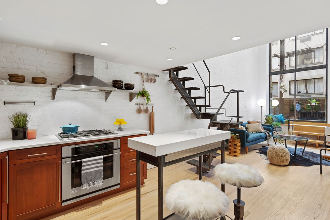 A kitchen with hardwood floors, a staircase next to it, and exposed white brick.