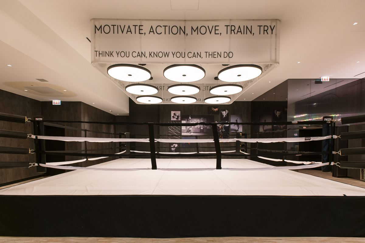 "A large boxing rings in the middle of room under nine circular lights. A sign above reads ""Motivate, Action, Move, Train, Try."""