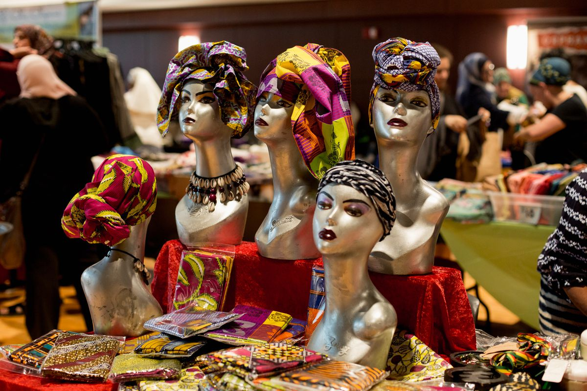 Mannequins wearing the gele at a table at the expo