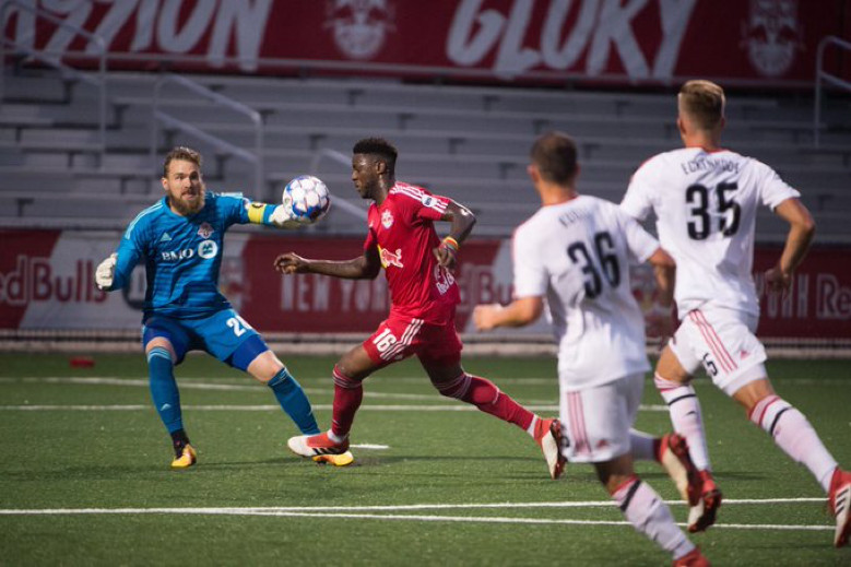 USL Photo - Toronto FC II's goalkeeper, Caleb Patterson-Sewell confronts New York Red Bulls II's Anatole Abang as he bears in on goal