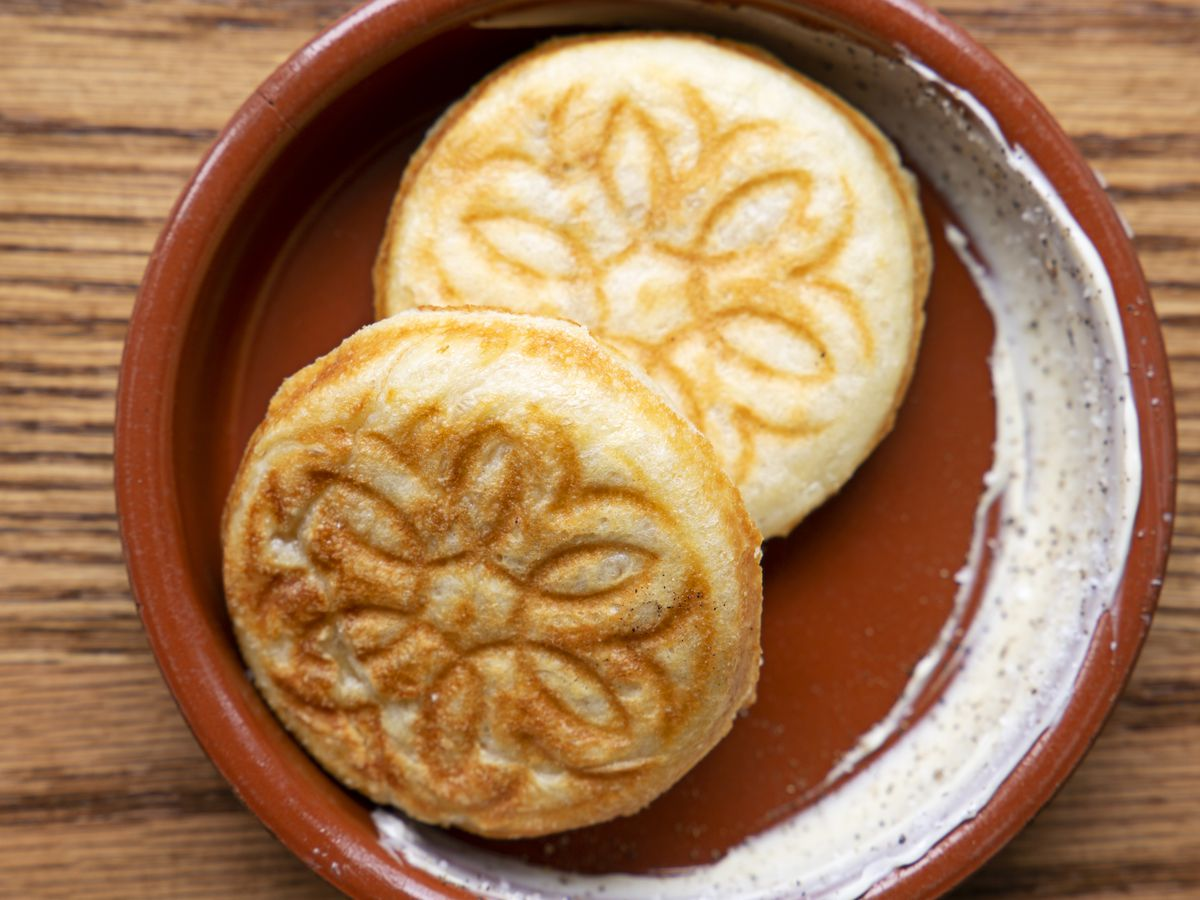 Two pieces of tigelle, a round bread from Modena, Italy, that's made in a special cast-iron pan