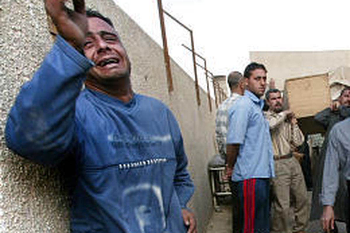 A man cries as the coffin of his mother, killed by a car bomb explosion at a market, is carried outside a hospital in Baghdad.