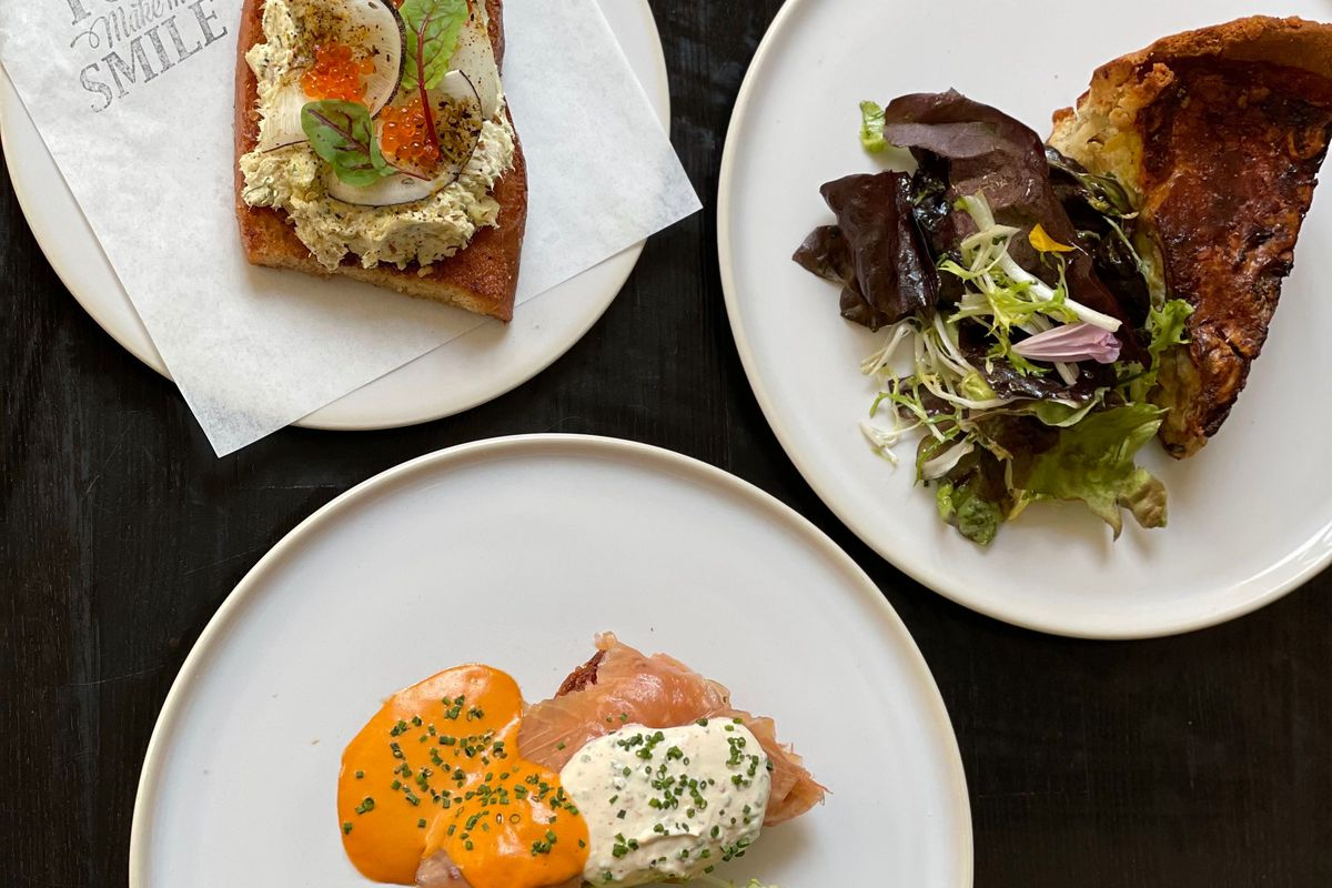 three tartines with salmon, eggs, and salad on white plates with a napkin that reads you make me smile