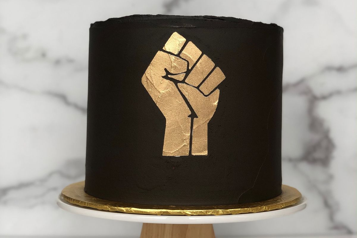 Natty Cakes' Black Lives Matters cake, a black cake with the Black Lives Matters raised-fist logo in gold.