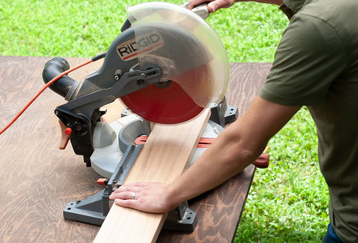 Man Cuts Wooden Boards For Table And Benches With Miter Saw