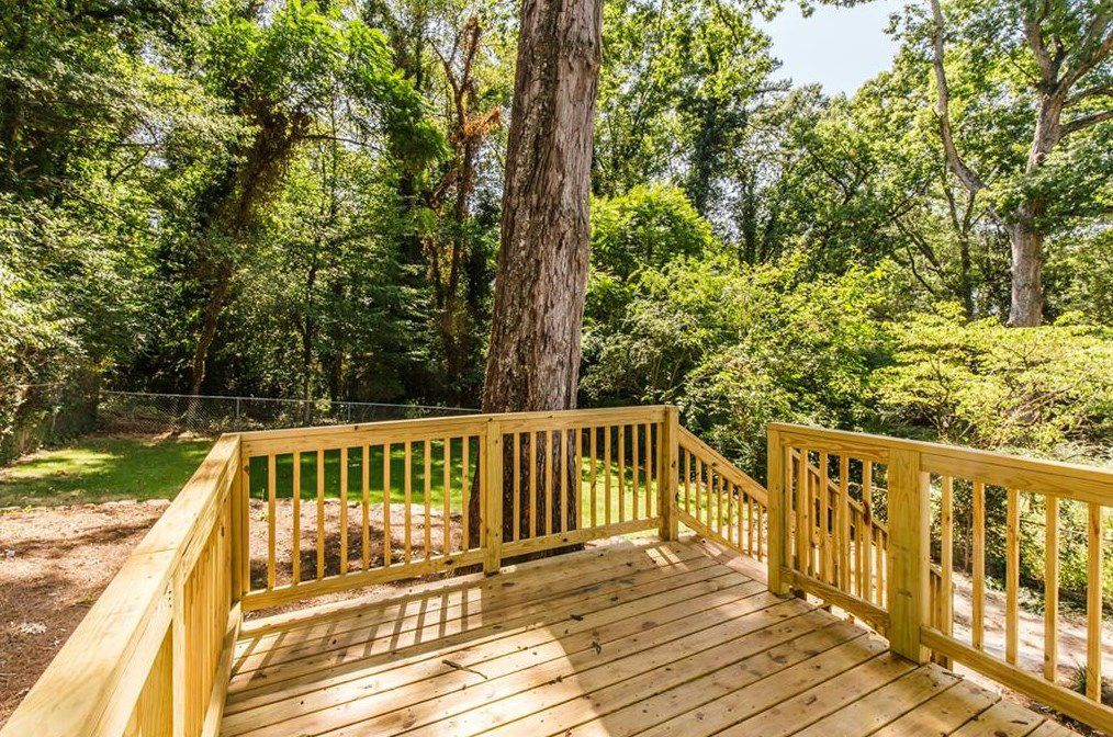 A backyard with tall trees and a new deck.