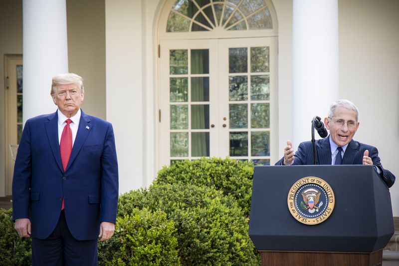 Doctor Anthony Fauci speaks from a podium outside the White House while President Trump stands to one side.