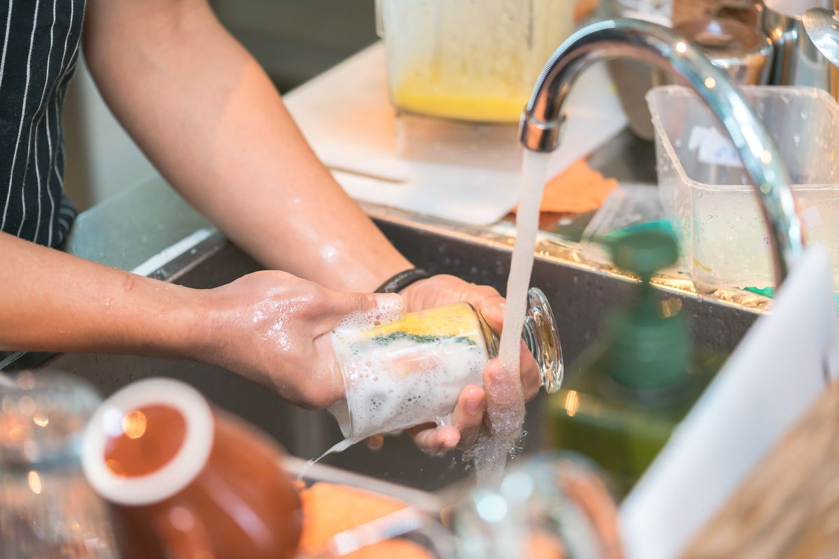A person washes a glass with a sponge