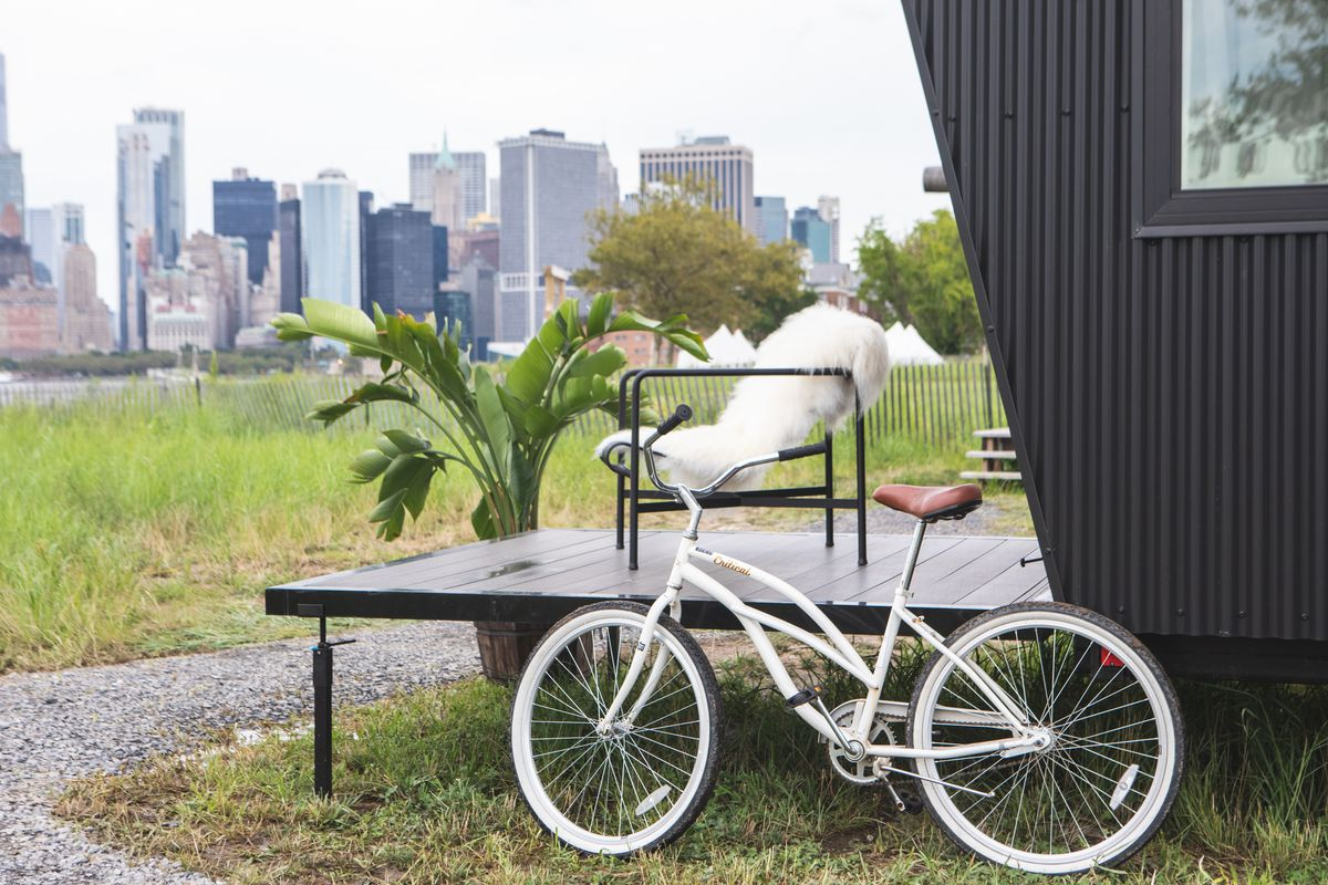 A deck attached to a tiny house that is parked on an island. A chair with a fuzzy white throw blanket is on the deck, which is painted black. A white bicycle is parked next to the house.
