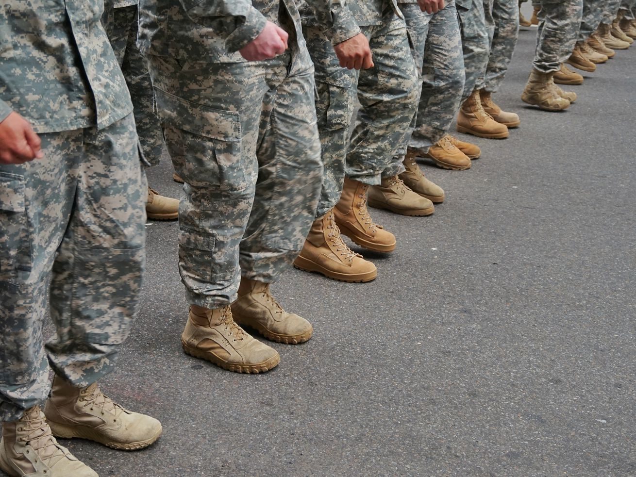 People in military uniform stand in line.