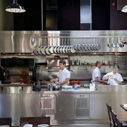 Chef de cuisine Michael Gaines preps on the left.