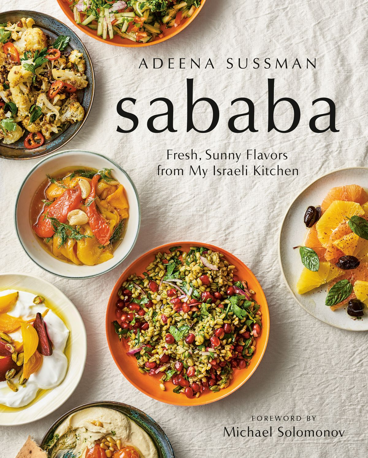 """Cover of """"Sababa"""" cookbook, showing several small colorful bowls of Israeli salads, on a beige rumpled tablecloth"""