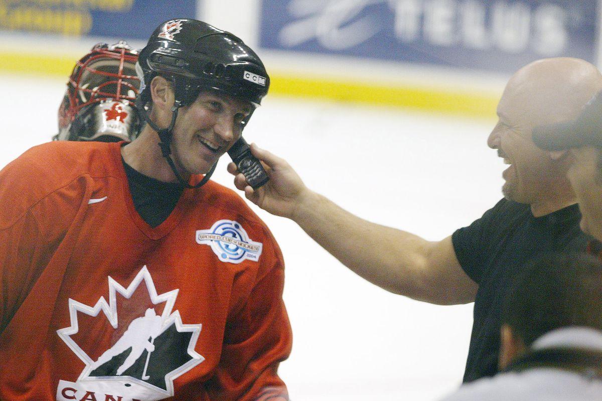 TEAM CANADA---08/26/04---Mario Lemieux takes a call via the phone of Massage Therapist Tom Plasko on
